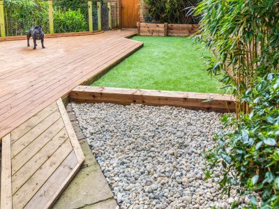 A section of a residntial garden, yard with wooden decking, patio over a fish pond, a section of artificial grass and an area of stone pebble. There is a bamboo plant and a dog in the garden.